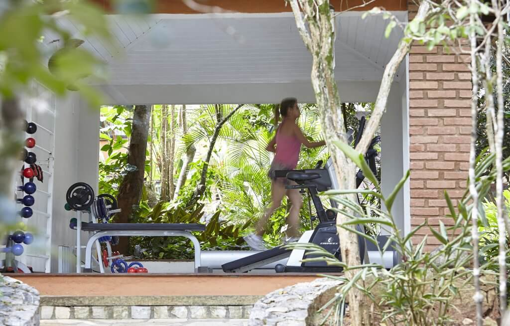 A photograph of a gym in a conservatory, with a woman running on a treadmill inside