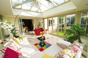 Interior shot of a conservatory decorated with colourful sofas, rugs, cushions, and a lamp.