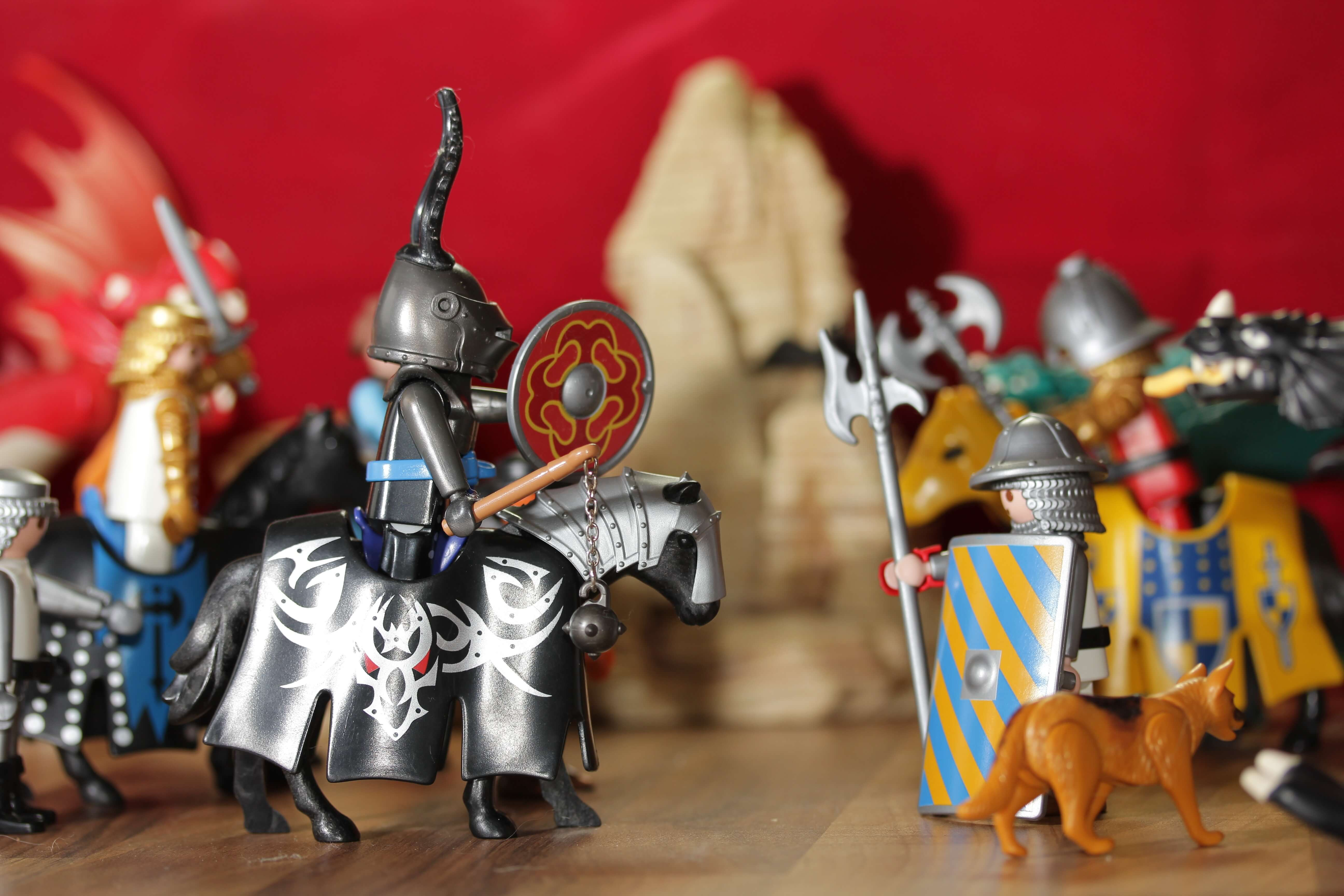 A photograph of medieval Playmobil children's toys, including a knight on a horse with a lance, as well as spearmen