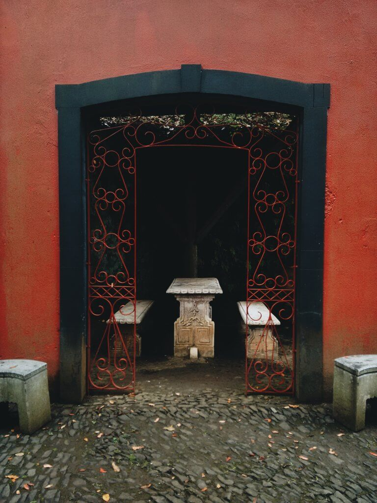 A photograph of an open entryway to a passage with seating. The walls around the doorway are red, as is the metalwork around the archway.